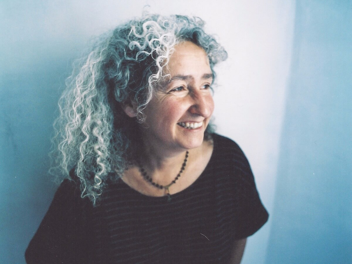 A photo of Nora Guthrie looking to the side with a blue and white wall behind her.